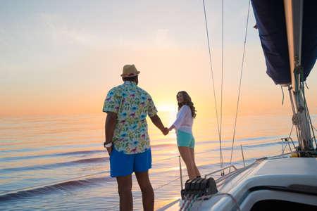 Reis rond de wereld op een jacht. Liefdesverhaal. Huwelijksreis op een zeiljacht. Yacht bij zonsondergang. Datum van de jongen en meisje op een jacht. Reis rond de wereld.
