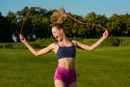 woman rope: Girl jumping on jump rope with a smile. Girl doing a workout outdoors. Girl engaged in sports on a green grass. Stock Photo