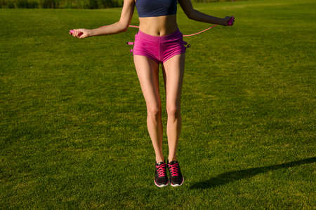 woman rope: Close-up of jumping legs on the jump rope. Outdoor sports. Girl jumping on a skipping rope on a green grass. Stock Photo