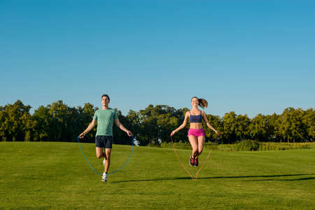 a young man: Sports on the street. Guy and girl are jumping on the jump rope. Young sportsmen do warm-up on a golf course.