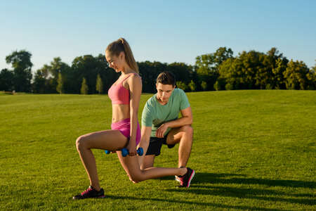 sports activities: Fitness trainer plays sports with a girl. Sports activities at the stadium. Outdoor sports. Young people engaged in sports. Stock Photo