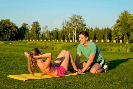 pres: Trainer is engaged in sports with a girl on the green grass. Girl shakes her pres on the park. Outdoor sports.