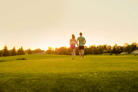 Guy and girl running on the green zone. Clean environment. Healthy lifestyle. Sports jogging outdoors. Running athlete.