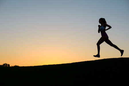 sport and leisure: Girl runs on the background of a beautiful sunset. Sport girl.Morning cross-country on golf field. Stock Photo