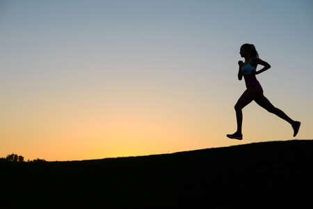 Meisje loopt op de achtergrond van een prachtige zonsondergang. Sport girl.Morning cross-country op golfgebied.