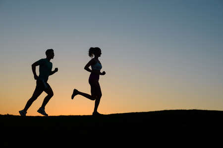 run woman: Morning run on the nature. Guy runs on the evening meadow. Sports jogging outdoors. Running sports. Stock Photo