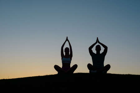 persone relax: Morning yoga on the nature. Silhouette figures of people at sunset. People relax. Rest at nature. Boy and girl meditating at sunset.