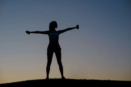deportista: Chica dedica a los deportes en la naturaleza. Silueta de la figura del atleta. La muchacha sacude sus m�sculos en el atardecer de fondo. La aptitud de la ma�ana en la naturaleza.