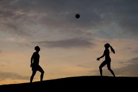 voleibol: Niño y niña jugando voleibol en la naturaleza. Jugar voleibol en el fondo del atardecer. Voleibol en las vacaciones. Voleibol de playa.
