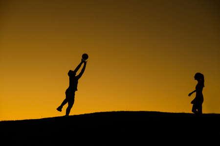 voleibol: Jugar voleibol en el fondo del atardecer. Niño y niña jugando voleibol en la naturaleza. Voleibol en las vacaciones. Voleibol de playa.