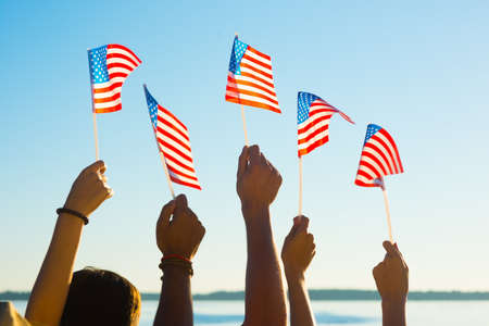 usa flags: People waved flags. Fans with American flags. Patriots waving flags of America. People at sporting events supported by America. Stock Photo