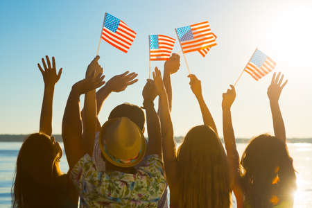 Guys and girls waving American flags. Football fans. Sports fans support their favorite team. Patriots of America.