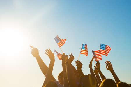 banderas america: Fans en el concierto de tus estrellas favoritas del pop. Los jóvenes con banderas americanas. Los aficionados en el partido con los brazos en alto. El orgullo en su país. Foto de archivo