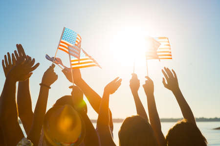 American flag. Fans meet idol. Crowd of waving American flags. Party on the waterfront. Concert in the resort town. Patriots of their country. Banco de Imagens