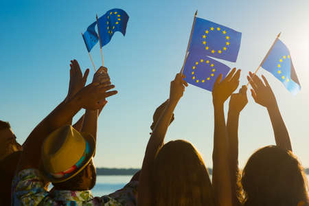 rooting: People with raised hands waving flags of the European Union. European dream. Future of Europe. European flag. Fans from Europe rooting for their team.