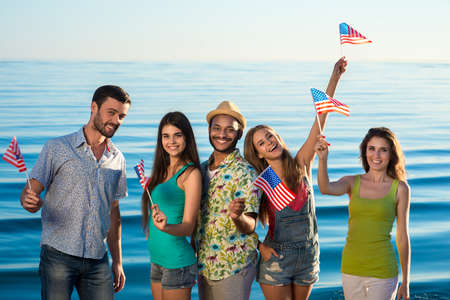 usa flag: Guys and girls with American flags on the beach. Patriots of America. Young people having fun.