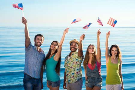 banderas america: compañía de amigos agita la bandera americana. Americanos que agitan de su país. Vacaciones a del mar. Chicos y chicas en el complejo. Foto de archivo