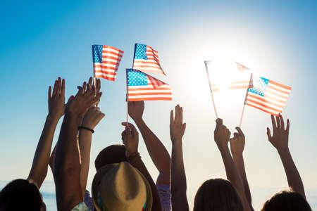 석양에 미국 국기를 흔들며 젊은 사람들. 남자와 미국 국기와 여자. 애국 자. 플래그는 바람에 빨라.