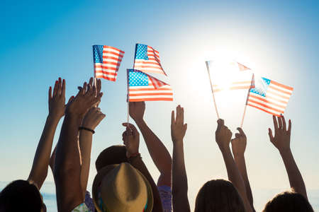 Young people waving American flags at sunset. Guys and girls with American flags. Patriotic party. Flags  flutters in the wind. Фото со стока