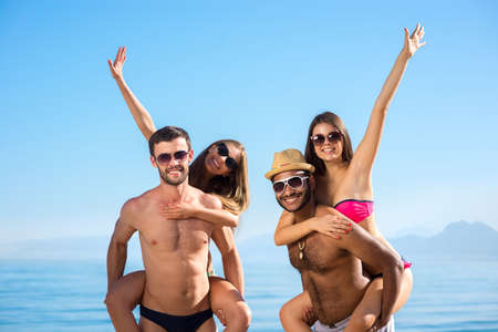 enjoyed: Guys and girls enjoyed holiday. In love couple on vacation. Weekend on the islands. Young people sunbathing on the beach. Young people smiling. Summer vacation at the resort. Stock Photo