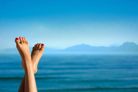 Feet of girl on the background of mountains. Girl at the resort. Female feet on sea background. Girl sunbathes on a beach. Meditation on the sea. Red pedicure.