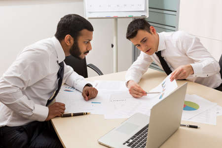 careerist: Businessmen are actively discussing the project. Successful young guys. Creative managers. Stock Photo