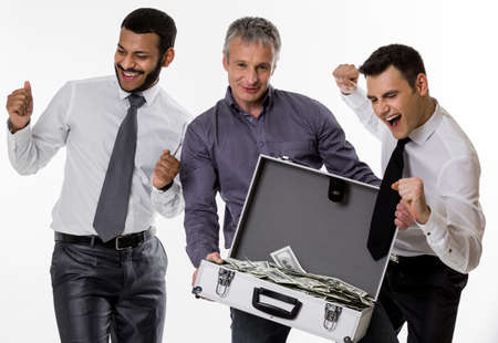 earned: Young people with a suitcase full of money. Businessmen have earned a lot of money. Successful people. Stock Photo