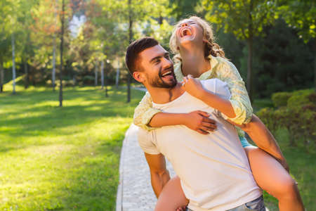 romantic date: Guy and a girl having fun in the park. Lovers enjoy each other. Romantic date in a beautiful park.