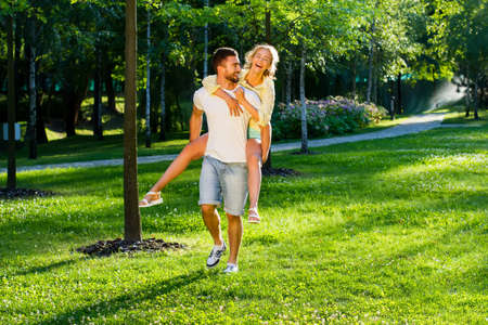 Playing in the park. Lovers enjoying a date. Romantic games. Guy bears the girl on the back.