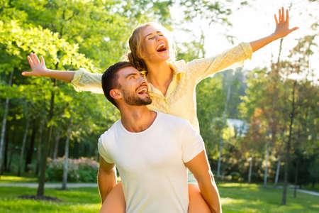 luna de miel: Feliz pareja de vacaciones. Los amantes están riendo. Chico y una chica feliz. Los amantes disfrutan de unos a otros en el parque de la tarde.
