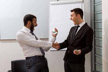 black handshake: Emotional guys rejoice the money. Managers keep the money. Salary.