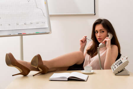 Sexy secretary. Seller consults the buyer on the phone.