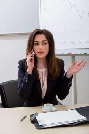 Business woman speaks on the phone. Administrator at the workplace.