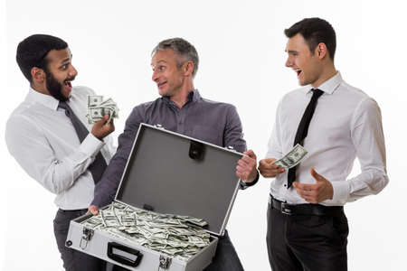 earned: Young people with a suitcase full of money. Businessmen have earned a lot of money. Stock Photo