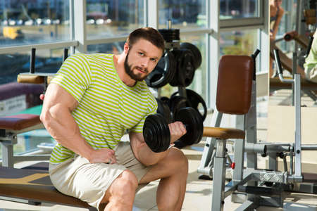 lusty: Man buiding up muscles with dumbbells. Bodybuilder in gym. Sportsman working out in gym.