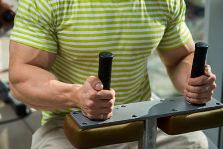 lusty: Sportsman in gym. Strong man develops the definition of muscles. Close-up picture of strong hands.