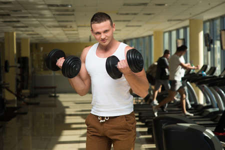 muscle guy: Guy in gym. Young sportsman working out in gym. Guy with two dumbbells in hands. Stock Photo