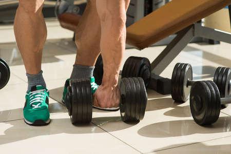 lusty: Bodybuilder picks up dumbbells. A few dumbbells on the floor. Muscular man�s hand taking dumbbell.