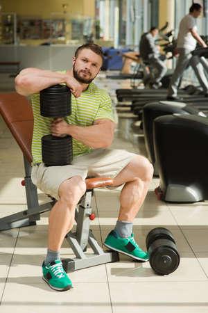 lusty: Sportsman in gym. Bodybuilder sitting in gym. Man keeps dumbbell in hand. Dumbbells on the floor near mans feet. Stock Photo
