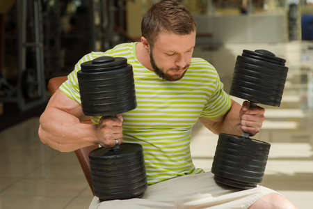 muscle gain: Close-up picture of athlete. Sportsmen sitting in gym. Man keeps two dumbbells in hands.