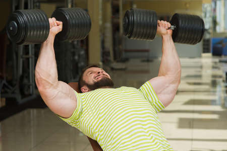 lusty: Bodybuilder in gym. Sportsman working out in gym. Man buiding up muscles with dumbbells. Stock Photo