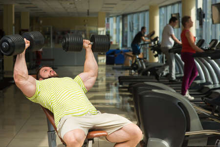 lusty: Champion with dumbbells. Sportsman working out in gym. Man doing exercises in gym with dumbbells. People training on the background. Stock Photo