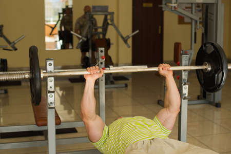lusty: Bodybuilder lifts weights. Athlete working out in gym. Man training in gym on the background. Stock Photo