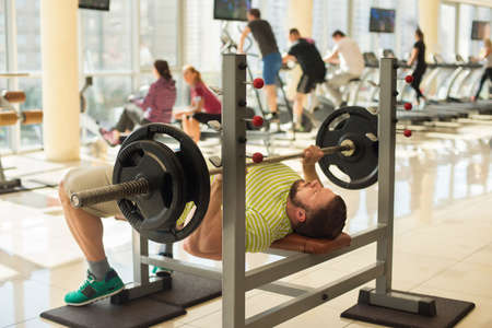 lusty: Sportsman with barbell. Sportsman lifting weights. Man doing weightlifting. Many people are training in gym on the background. Stock Photo