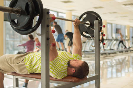 lusty: Strong man with barbell. Sportsman concentrated on the sport. Brutal man is pushing barbell.