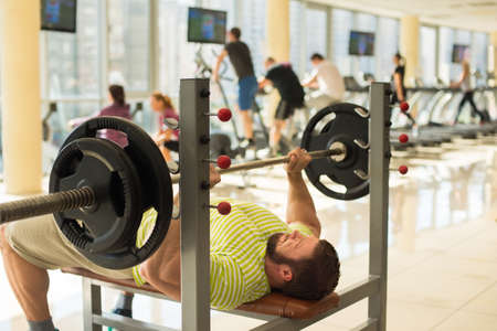lusty: Athlete with barbell. Bodybuilder pushing barbell. People training in gym on the background. Stock Photo