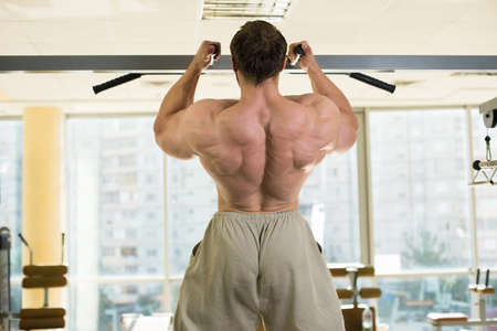 pullups: Champion doing pull-ups. Strong man doing pull-ups. Muscular back of bodybuilder training. A window on the background.