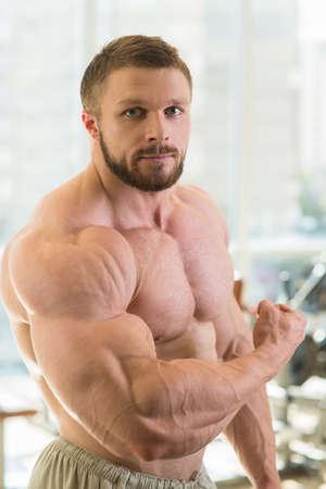 Gespierde man. Sterke gespierde man zoekt direct op de camera. Bodybuilder met enorme spieren.