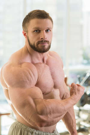 man gym: Muscular man. Strong muscular man looking straight at the camera. Bodybuilder with huge muscles.