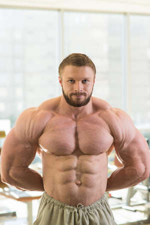 lusty: Muscular bodybuilder. Strong sportsman in gym. Muscular torso and arms. Very strong man looking at the camera.
